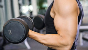 Man exercising biceps with dumbbells