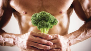 Healthy man holding broccoli