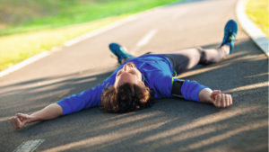 Man lying on running track after HIIT workout