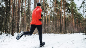 Man running in snow - winter exercise