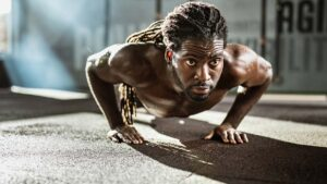 Athlete exercising push-ups in a gym.